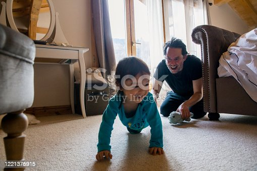 A father chases his son in the bedroom as he crawls around.