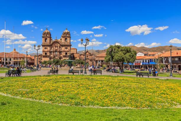 Plaza de Armas Hauptplatz mit Kathedrale und gelben Blumen im Vordergrund, Cuzco, Peru – Foto