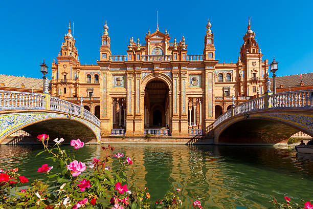 Plaza de Espana at sunny day in Seville, Spain Spain Square or Plaza de Espana in Seville in the sunny summer day, Andalusia, Spain. Flower beds, bridges and channel in the foreground seville stock pictures, royalty-free photos & images