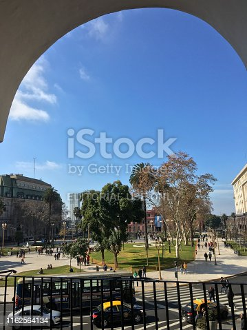 Buenos Aires, Argentina - July 14, 2019: Framed view of Plaza de Mayo square with Casa Rosada at the background from one of the many arches of the city Cabildo. This historical building was used as seat of the town council during the colonial era and the government house of the Viceroyalty of the Río de la Plata and is a city icon. Now it holds a free entrance museum that anyone can visit