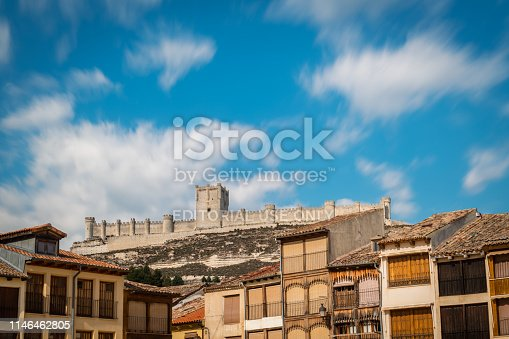 Traditional houses around the Plaza del Coso square in Peñafiel, Valladolid, with the medieval castle in the background. Long exposure.