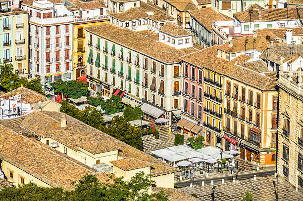 Plaza Nueva - Granada, Spain Granada, Spain - August 14, 2015: Plaza Nueva in Granada, Spain. Photo taken from Alhambra hill and overlooks the entire plaza and town. There are people and businesses represented in the photo. palace of charles v stock pictures, royalty-free photos & images
