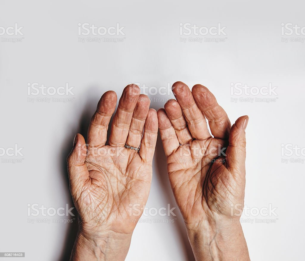 Pleading hands of old woman stock photo