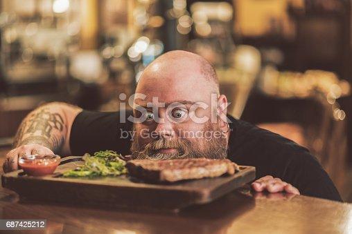 istock Pleasant adult guy having dinner in pub 687425212
