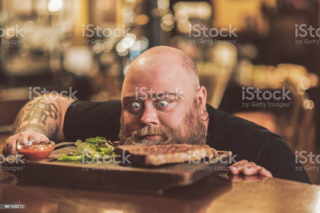Pleasant adult guy having dinner in pub stock photo