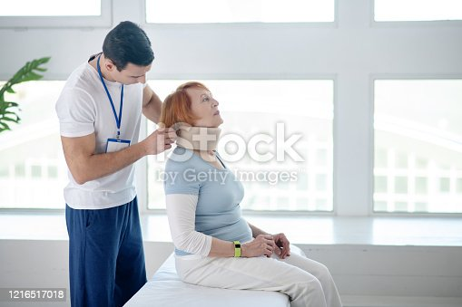 Neck collar. Pleasant aged woman sitting in a cervical collar while undergoing medical therapy