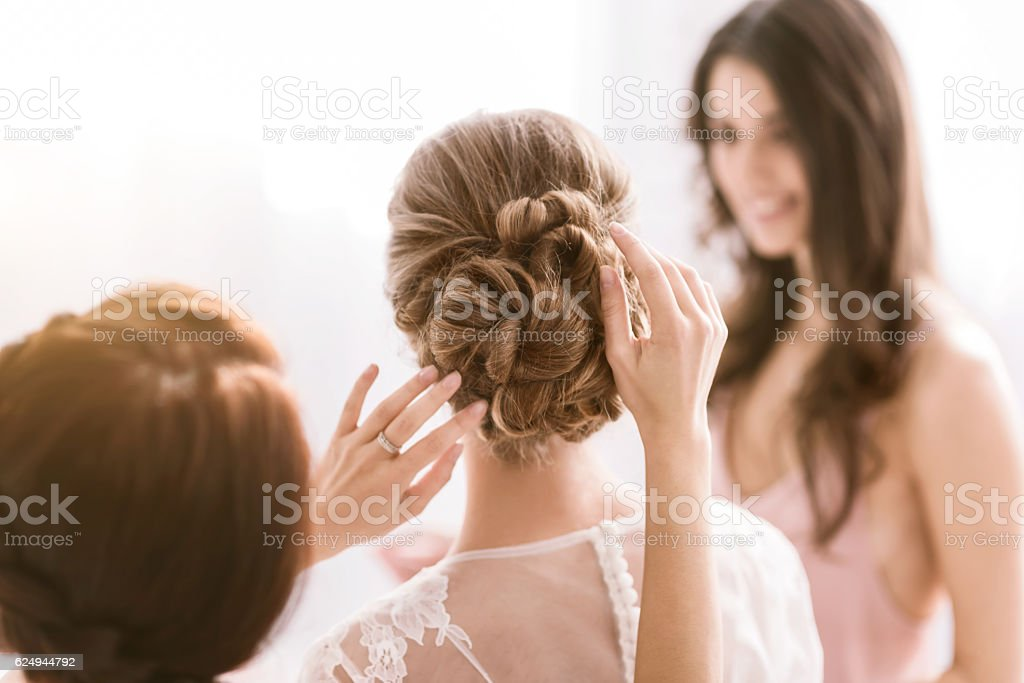 Pleasant bridesmaids helping the bride with her hairstyle stock photo