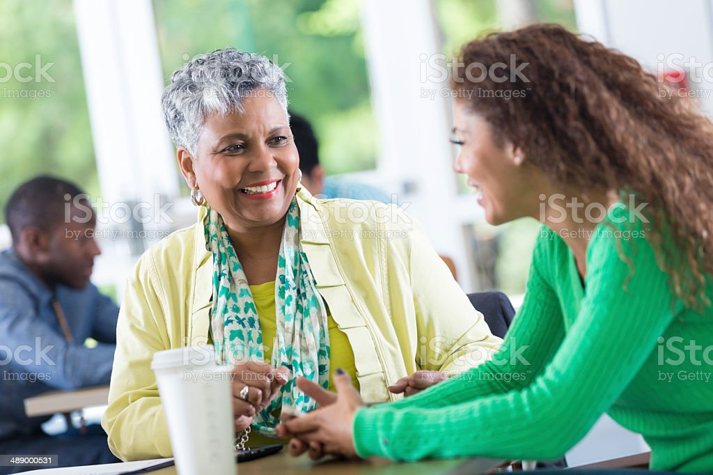 Pleasant businesswoman listening to co-worker at workplace breakroom stock photo