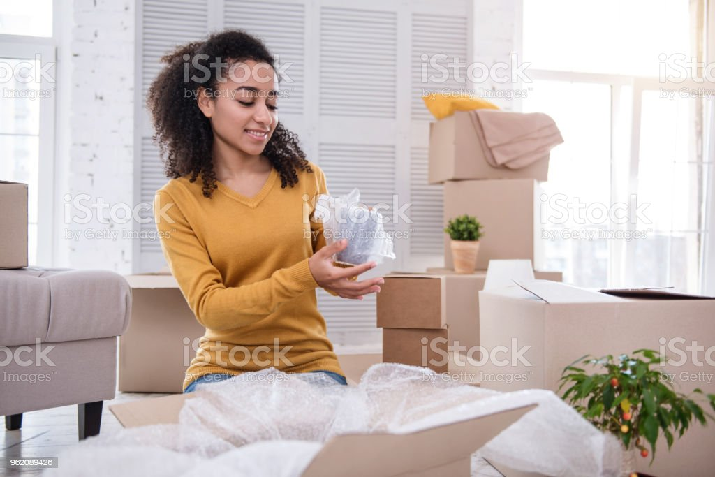 Pleasant curly-haired girl wrapping her tea cup stock photo