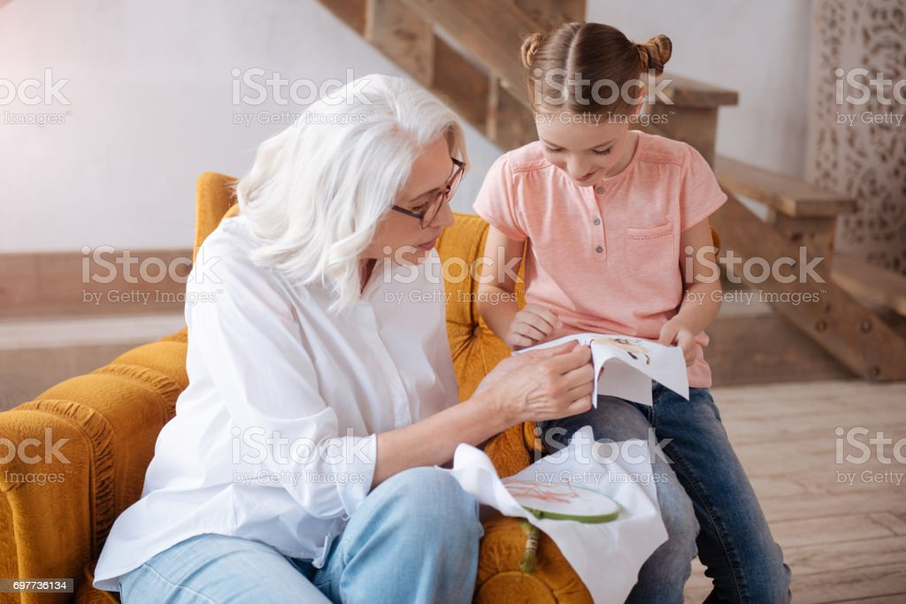 Pleasant delighted woman teaching to embroider stock photo