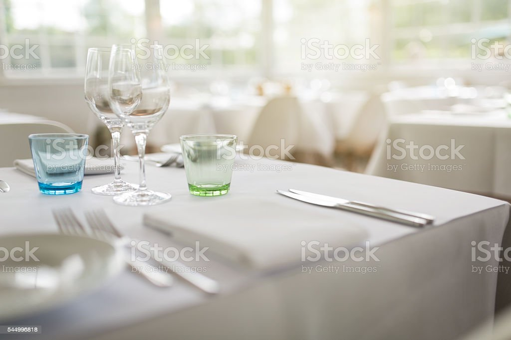 Restaurant table with two pairs of drink glasses, cutlery, plate and...