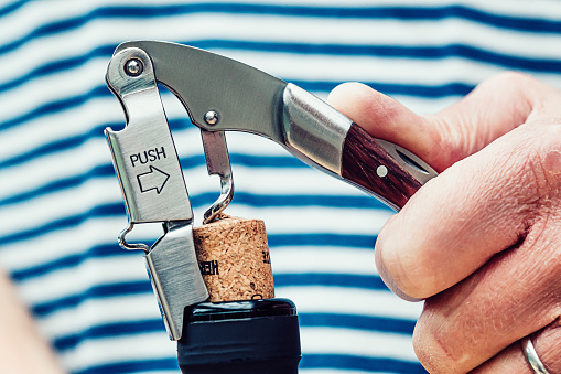 Close up of the removal of a cork from a wine bottle. The opener is the type which lifts the cork in two stages.