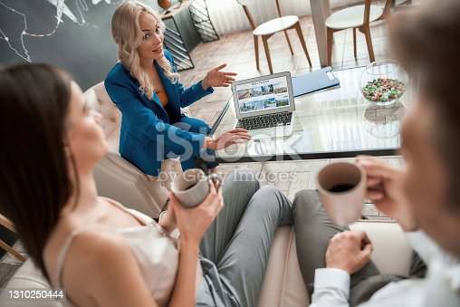 istock Pleasant female manager at the travel agency office sitting with her clients, young couple, using laptop and showing vacation ideas 1310250444