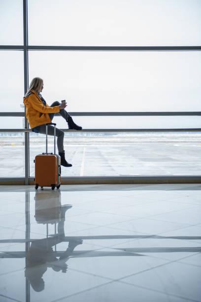 pleasant girl is enjoying view at airport - donna valigia solitudine foto e immagini stock