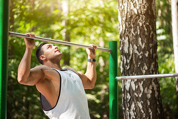 pleasant hard working man doing chin ups - horizontal bar stock photos and pictures