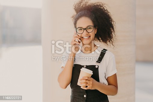Pleasant looking curly teenage girl wears transparent glasses, talks on mobile phone, has coffee break, dressed in white t shirt and overalls, enjoys spare time and conversation. People and technology