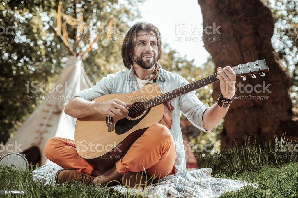 Homem agradável com guitarra sentado na grama - foto de acervo