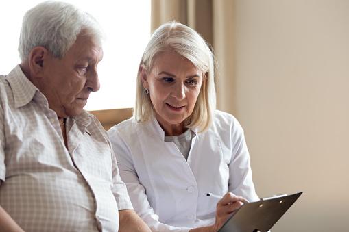 istock Pleasant middle aged female doctor explaining medicine prescription to patient. 1189748867