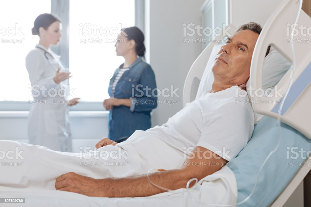 Pleasant middle aged man resting in his bed stock photo