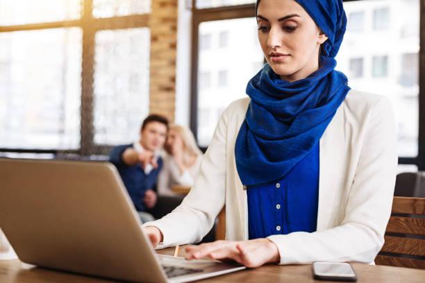 pleasant muslim businesswoman working on the laptop - vorurteil stock-fotos und bilder