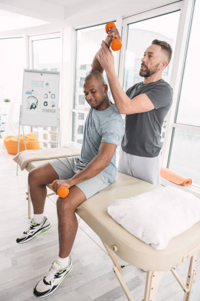 Pleasant nice man lifting dumbbells Professional therapy. Pleasant nice man sitting in the therapist office and lifting dumbbells drug rehab stock pictures, royalty-free photos & images