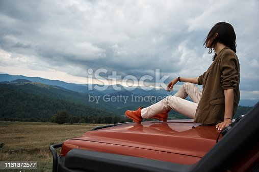 1131372580 istock photo Pleasant nice woman resting on the car hood 1131372577