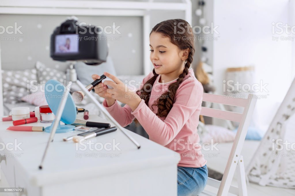 Pleasant pre-teen girl filming entry for her beauty vlog stock photo