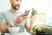 Pleasant satisfied man using cellphone and holding a broccoli