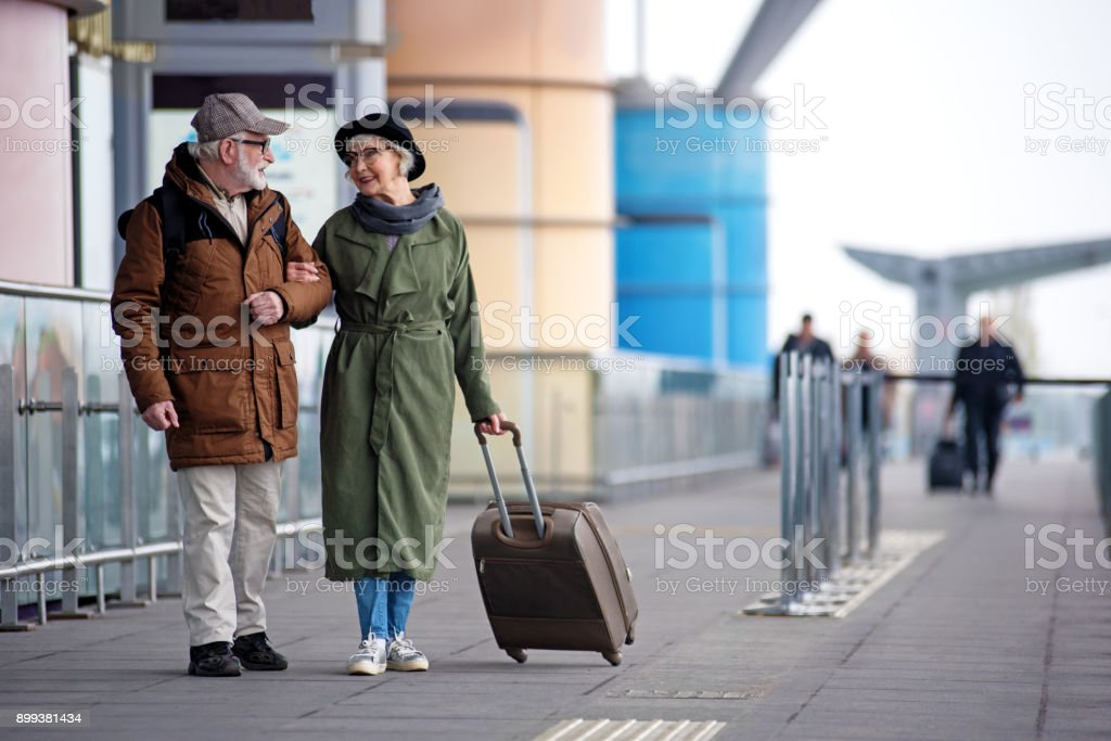 Pleasant senior couple is situating near airport stock photo