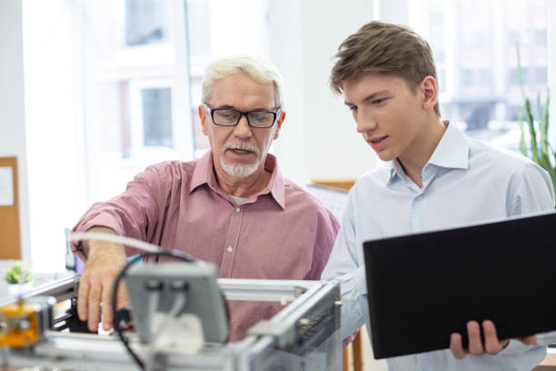 Pleasant senior engineer teaching about 3D printer Nice teacher. White-haired senior engineer teaching his young student about 3D printers and telling him about the work algorithm qualification round stock pictures, royalty-free photos & images