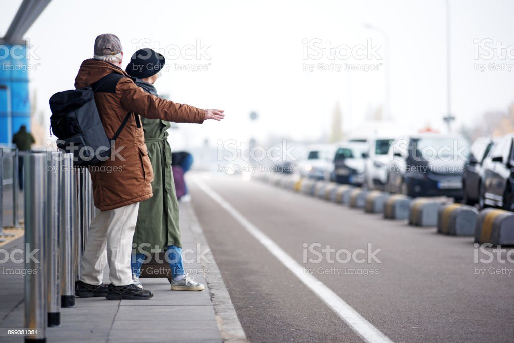Pleasant senior male and female are waiting for transport stock photo