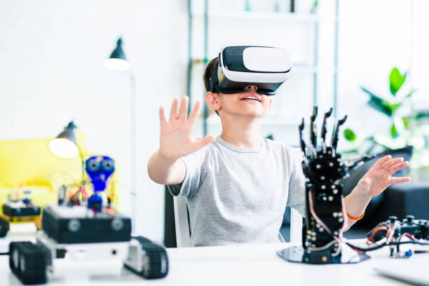 Pleasant smart boy testing VR glasses at home stock photo