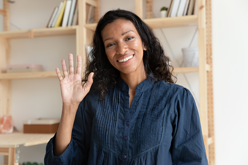 Head shot close up pleasant smiling biracial woman making hello gesture, looking at camera. Positive young african american teacher tutor coach greeting clients online before educational webinar.