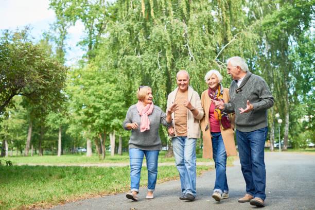 trevlig promenad på park - senior walking bildbanksfoton och bilder