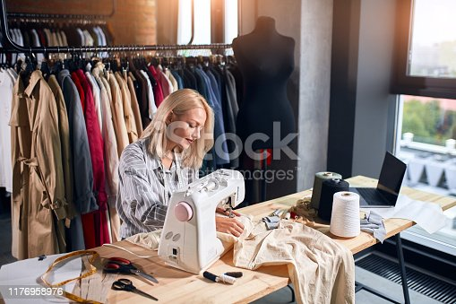 pleasant woman earning money,she sewing clients' clothes. close up photo.