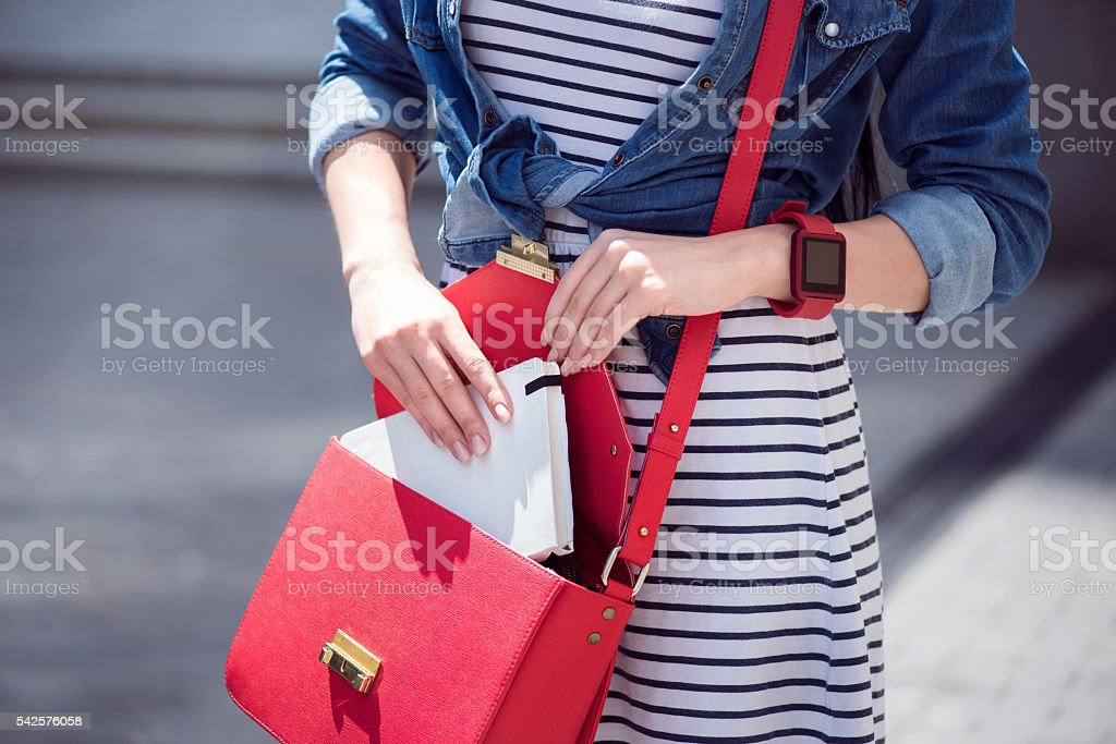 Pleasant woman putting book into her bag - foto de stock