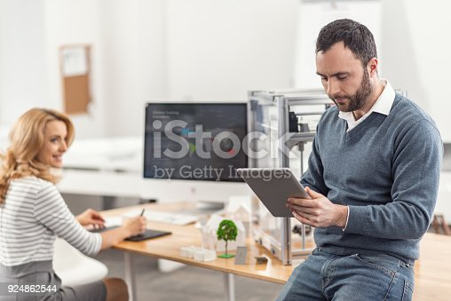 464482634istockphoto Pleasant woman watching her colleague work on tablet 924862544