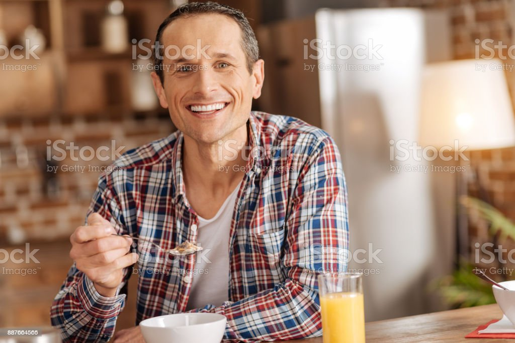 Pleasant young man eating cereals in the kitchen stock photo