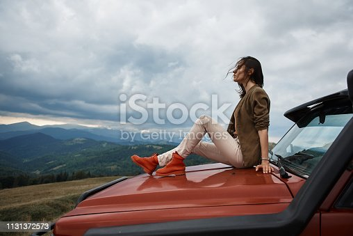 1131372580 istock photo Pleasant young woman lying on the car hood 1131372573