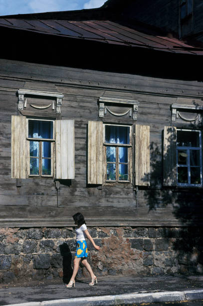 schöne junge frau, die vorbei an den alten russischen haus - typisch 90er stock-fotos und bilder