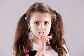 Female child with her finger on her lips, asking for silence