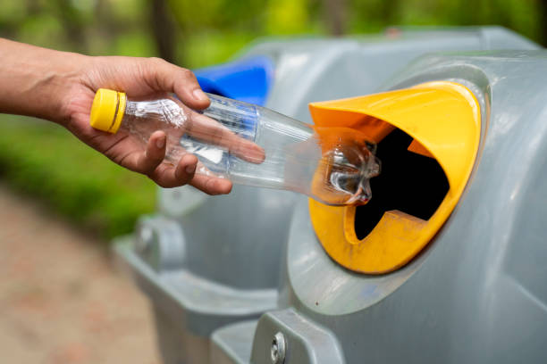 Please dispose of plastic bottle into the tank. A man throw rubbish in the trash can by separate garbage to dispose like hazardous waste , stock photo