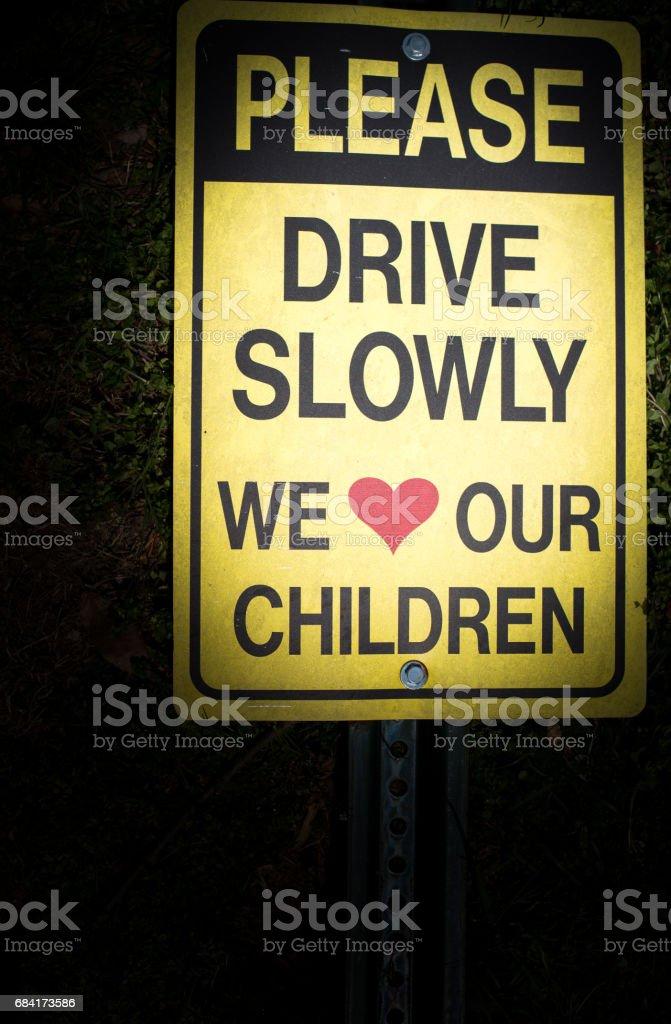 Vänligen kör långsamt vi älskar våra barn tecken royaltyfri bildbanksbilder
