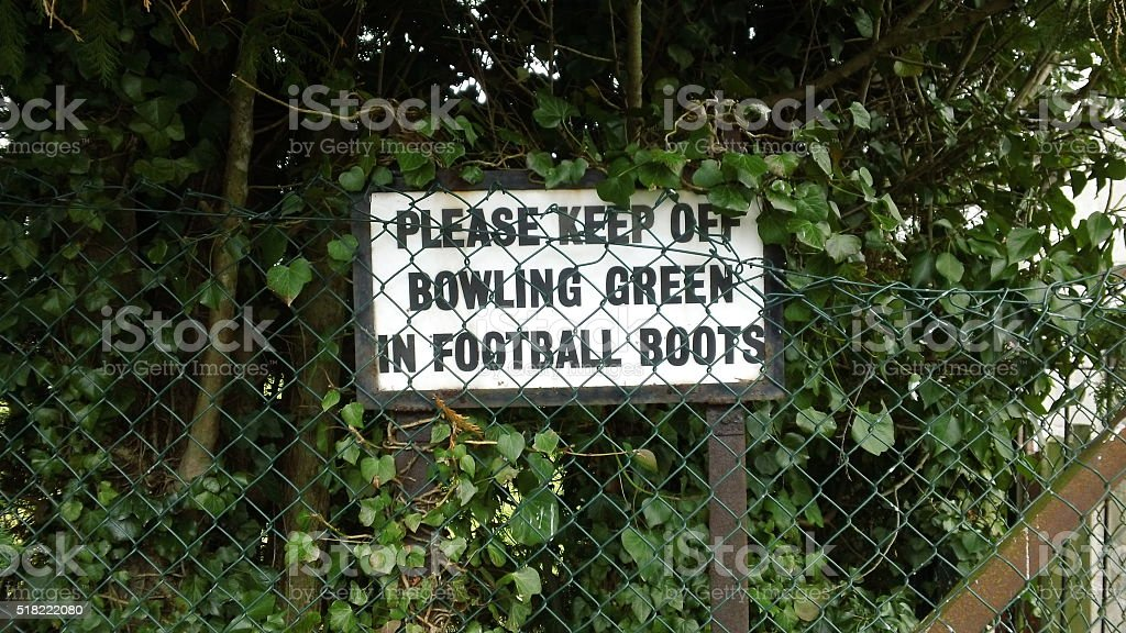 'Please keep off the bowling green in football boots' sign. stock photo