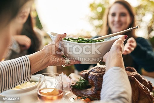 Shot of a unrecognizable woman passing on a plate of green beans to a cheerful woman at lunchtime over a table