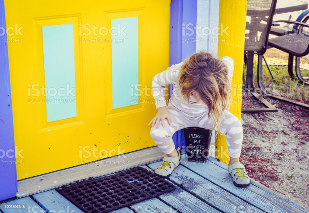 Little girl squats over a bucket intended for cigarette butts, in an...