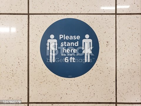Please stand six feet apart and social distance signs in blue and white are displayed on a tile floor due to COVID-19 as businesses and retail establishments begin to reopen.