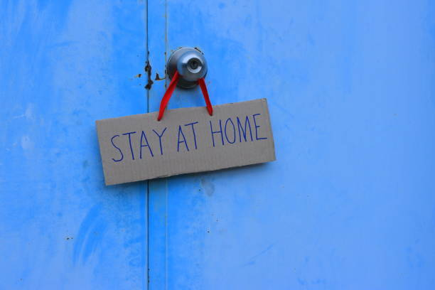Please stay at home closeup STAY AT HOME cardboard sign hanging on doorknob. Due to coronavirus outbreak, many countries use lockdown strategy illness prevention stock pictures, royalty-free photos & images