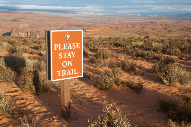 """Please stay on trail at horseshoe bend Page, AZ, USA – October 25, 2016: A sign saying """"please stay on trail"""" at Horseshoe Bend parking lot asking tourists and visitors to stay on trail on their way to Horseshoe Bend viewpoint horseshoe bend colorado river stock pictures, royalty-free photos & images"""