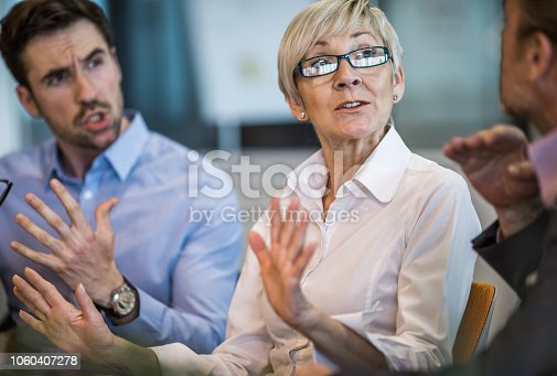 Senior businesswoman telling her colleagues to stop arguing on a meeting.